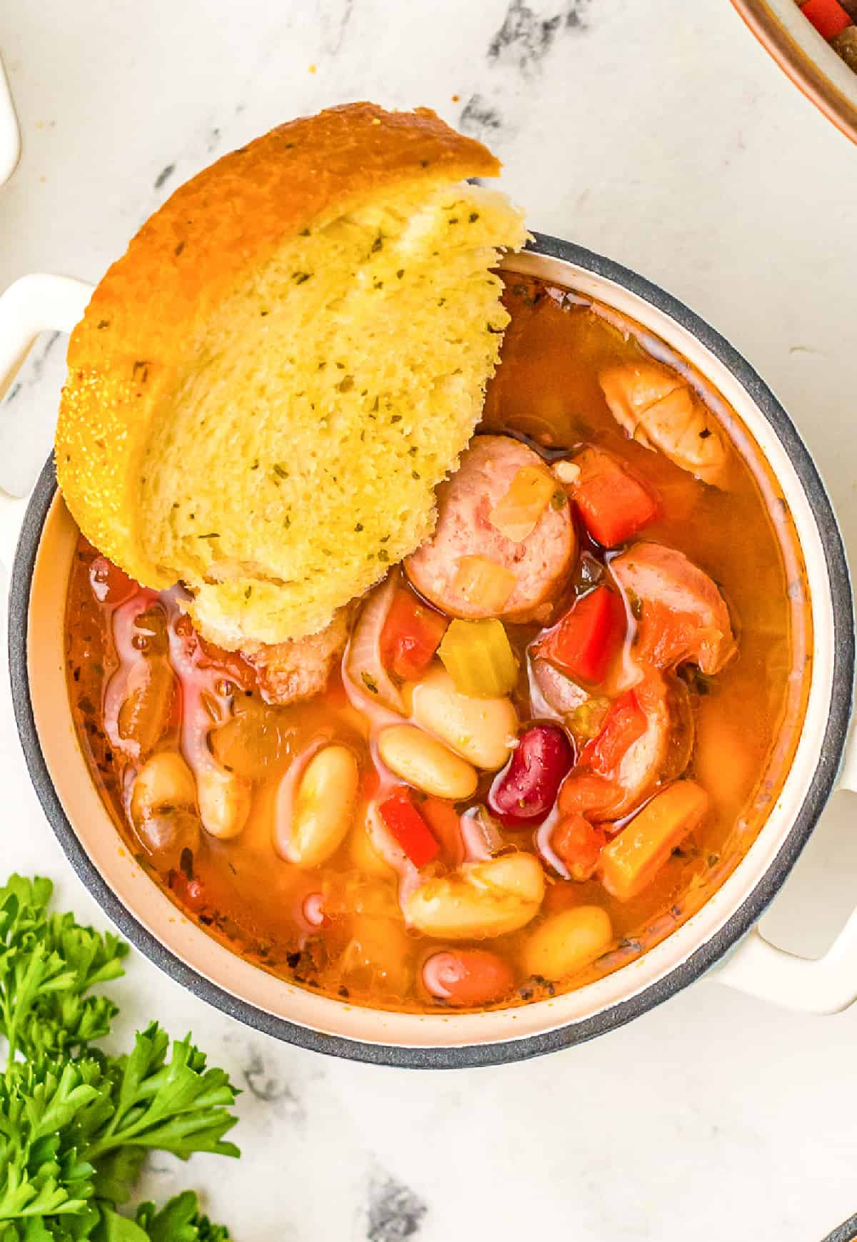 a small bowl of sausage bean soup with a slice of garlic bread.