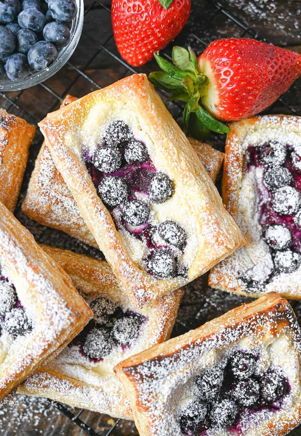 A pile of blueberry cream cheese pastries with a side of strawberries.