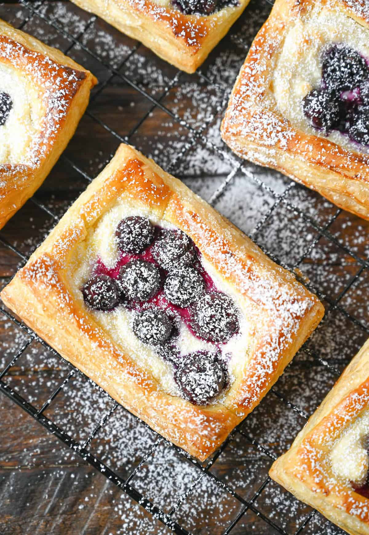 A blueberry cream cheese danish on a wire cooling rack.