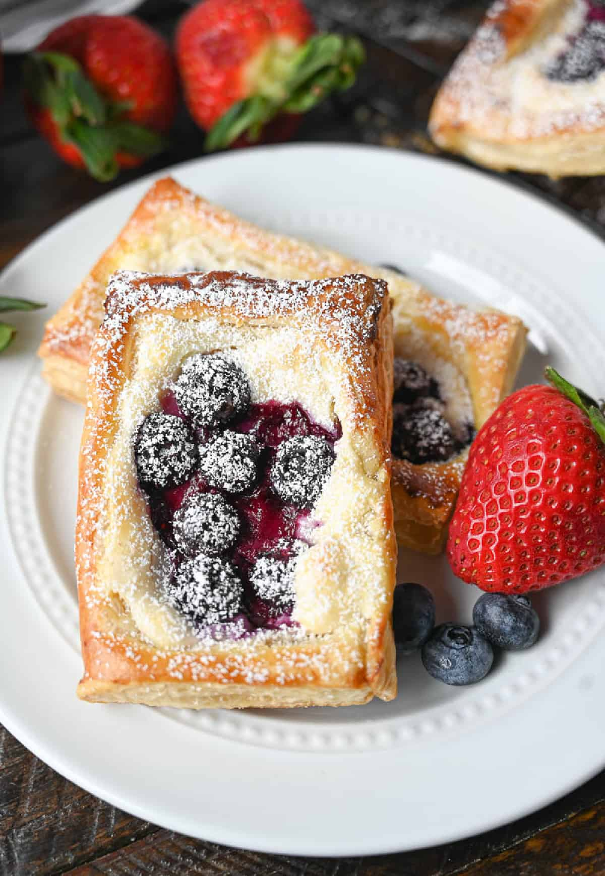 Two blueberry danishes on a small white plate.