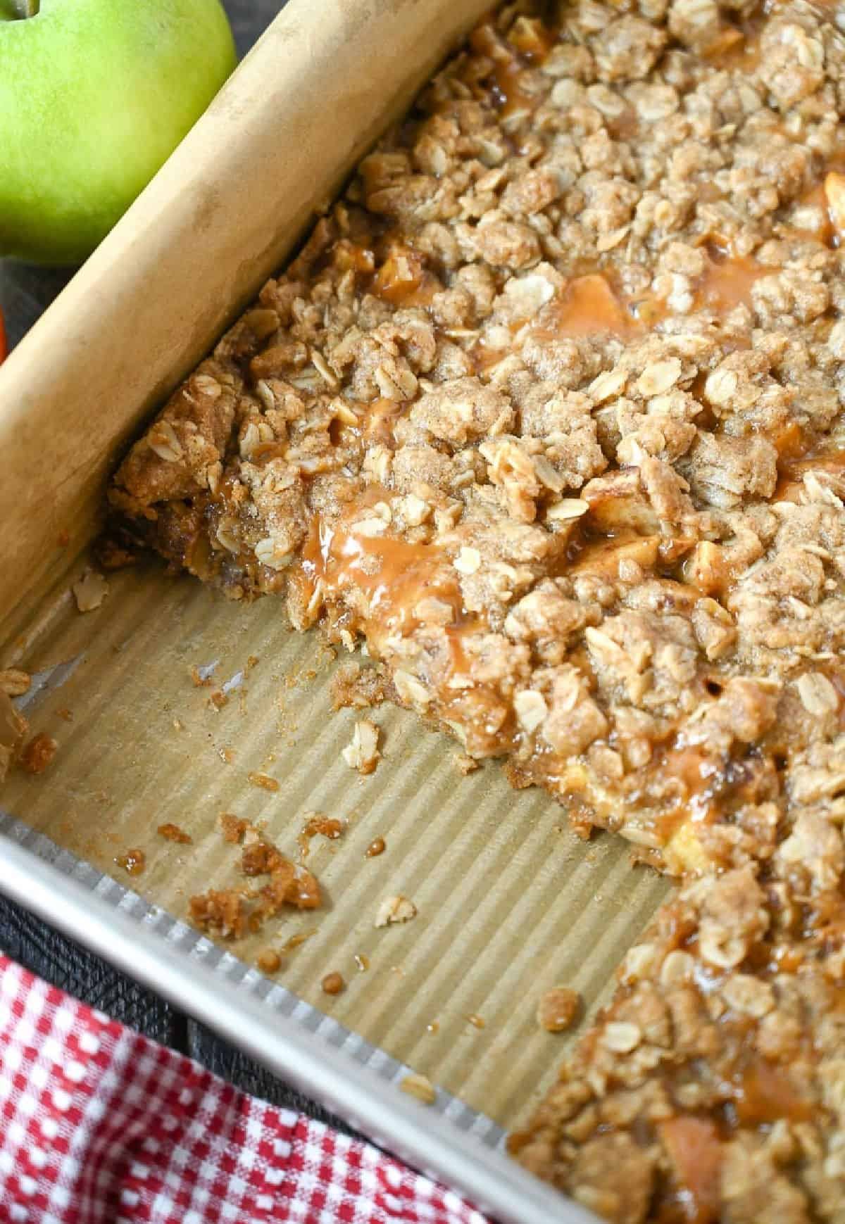 Caramel apple crumble in a metal baking pan with a few servings missing.
