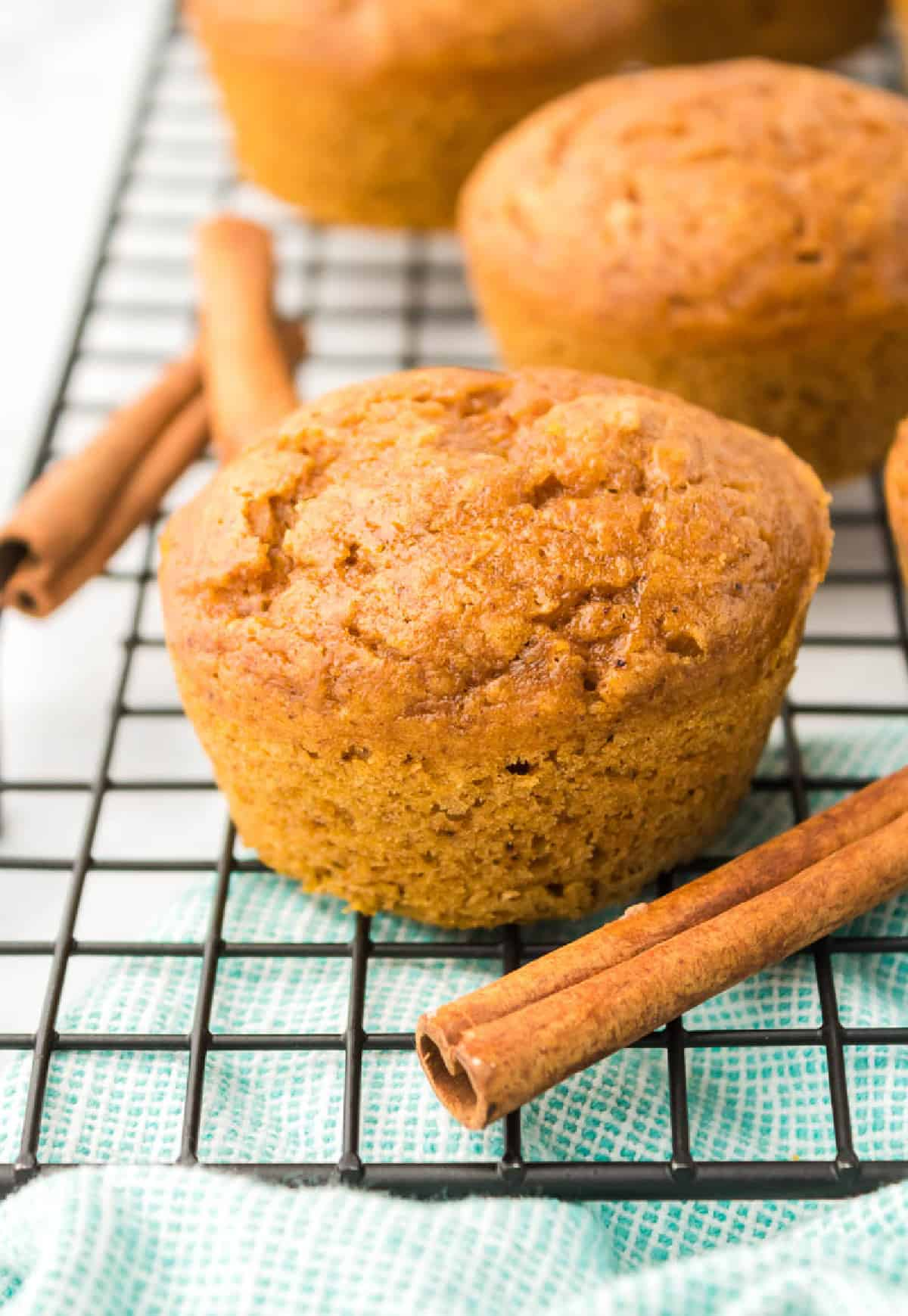 Onw muffin on a cooling rack with cinnamon sticks.