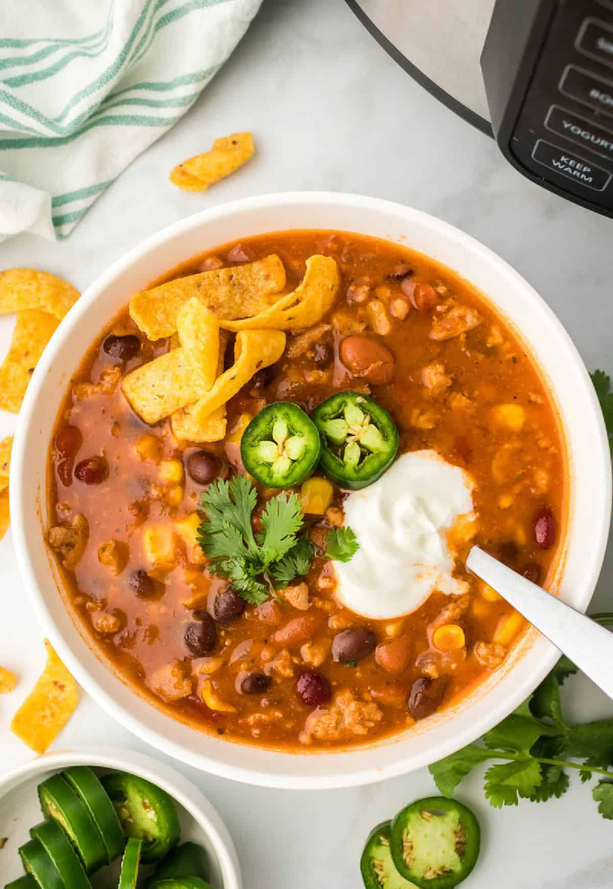 A close up photo of taco soup with sour cream and jalapenos on top.