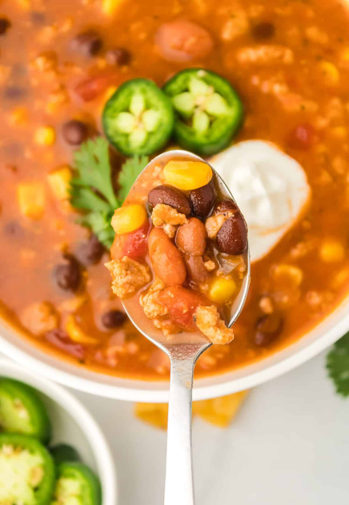 A spoon taking a bite out of a bowl of taco soup.