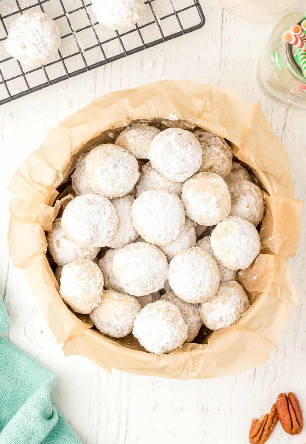 A pile of snowball cookies in a bowl.
