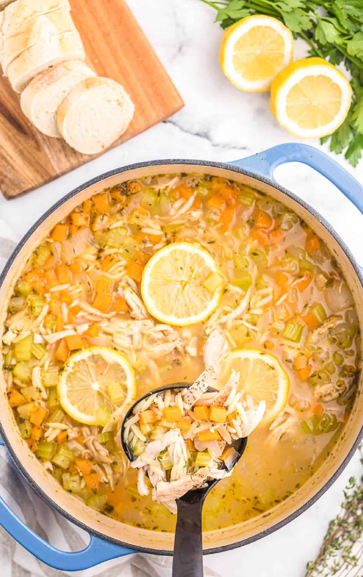 Homemade chicken orzo soup in a large pot with a black ladel.